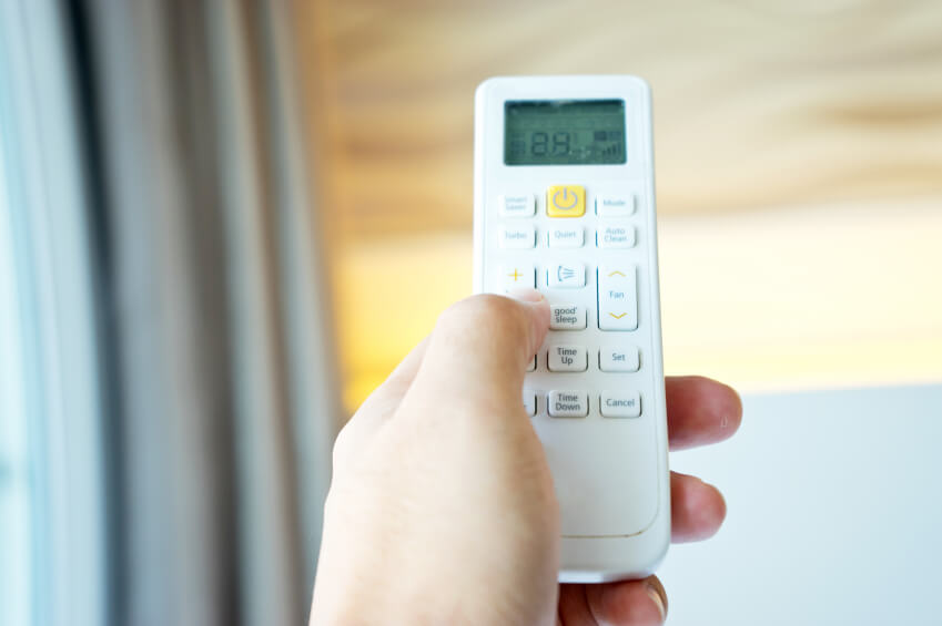Hand holding a remote control of air conditioner - home automation